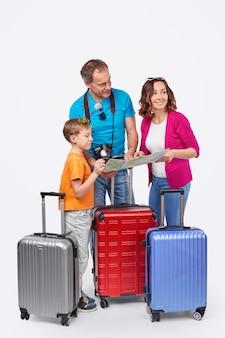 Genitori e figlio a figura intera con le valigie che sorridono e guardano lontano mentre leggono la mappa su sfondo bianco against