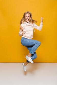 Foto a tutta lunghezza di una ragazza adorabile con apparecchi dentali che salta e stringe i pugni, isolata su sfondo giallo