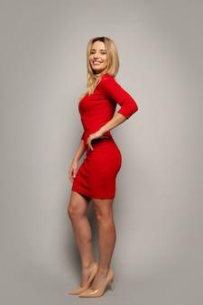Foto a figura intera di una bionda seducente in un vestito rosso, che posa di profilo, guardando nella telecamera con un sorriso radioso.
