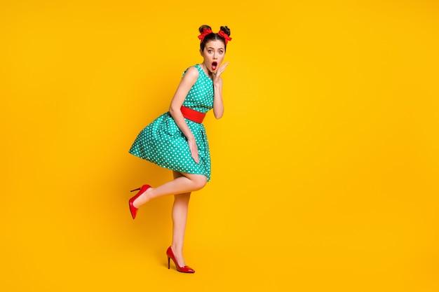 Foto a tutta lunghezza di una ragazza stupita che tocca il viso della mano indossa vestiti in stile verde acqua pinup isolati su uno sfondo di colore brillante