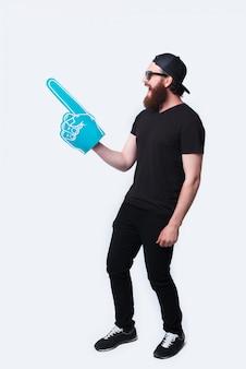 Foto a figura intera barbuto hispter uomo che indossa occhiali da sole e che punta con un grande guanto da fan