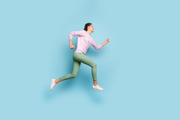 Foto a figura intera di bella signora che salta in alto correndo traguardo in esecuzione campione di maratona anima competitiva indossare casual maglione rosa pantaloni verdi isolati colore blu