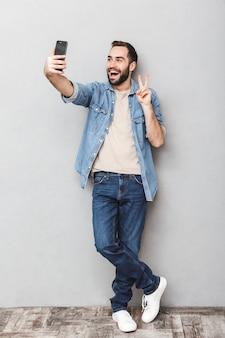Foto integrale dell'uomo caucasico castana che ha la barba che prende selfie sul cellulare e che mostra la pace canta isolata sopra la parete grigia