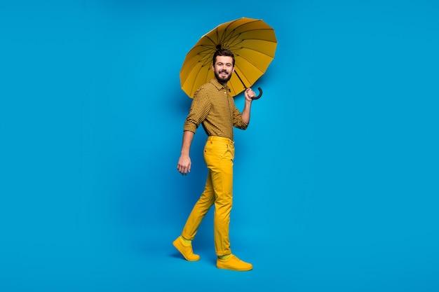 La foto a figura intera del ragazzo allegro si gode la primavera del tempo libero tenere l'ombrellone colorato lucentezza indossare scarpe di vestiti di bell'aspetto isolate su colore blu