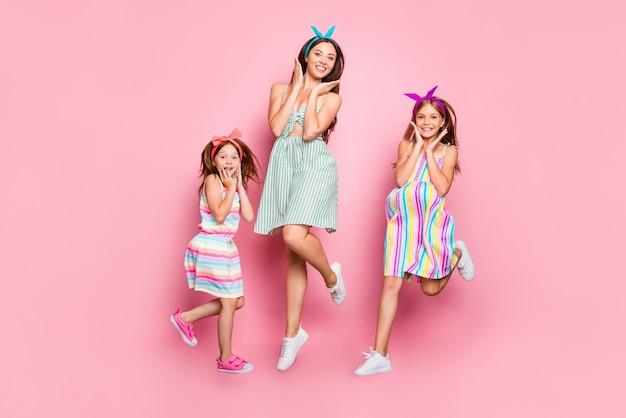 Foto a figura intera di donne allegre con fasce luminose che saltano indossando gonna abito isolato su sfondo rosa