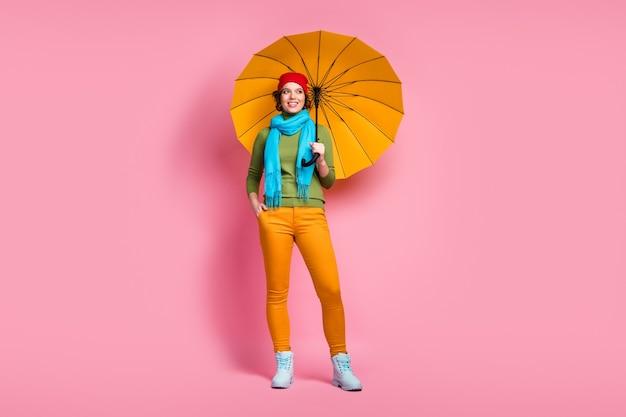 Foto a figura intera di allegra bella ragazza affascinante tenere il suo parasole brillante proteggere il suo look copyspace godersi le vacanze piovose indossare il ponticello di copricapo isolato sopra la parete di colore rosa