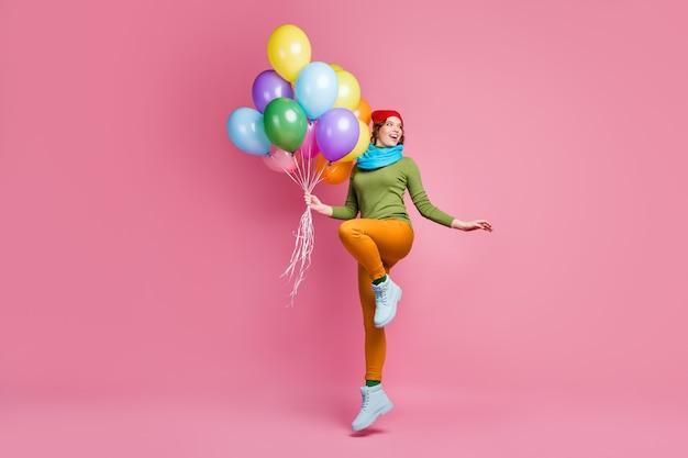 Foto a figura intera della ragazza millenaria allegra che salta tenere molti baloons di elio d'aria guarda copyspace goditi l'anniversario festivo invernale indossare calzature pantaloni isolati su muro di colore rosa