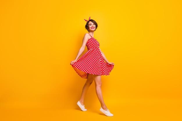 Foto a figura intera del contenuto bella ragazza godersi la primavera del tempo libero weekend andare a piedi toccare la sua gonna in stile vintage indossare scarpe da ginnastica bianche isolate su un muro di colore brillante