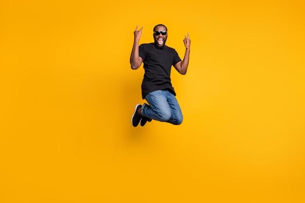 Foto a figura intera del ragazzo afroamericano funky pazzo salto divertente concerto rock urlo spettacolo corna indossare jeans denim stile giovanile isolato su backround di colore giallo Foto Premium