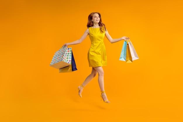 Foto a figura intera di una graziosa signora dai capelli rossi che porta molti pacchi della spesa, dipendente dallo shopping in abito giallo, gioioso centro commerciale isolato ove sfondo di colore giallo in studio