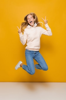 Foto a tutta lunghezza di una ragazza carina con bretelle dentali che salta e mostra segni di pace, isolata su sfondo giallo