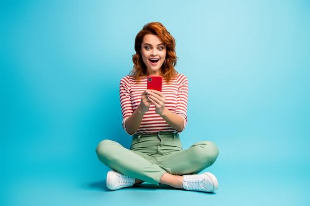 Foto a figura intera donna dipendente eccitata sedersi gambe incrociate uso smartphone leggere notizie incredibili sui social network urlo impressionato wow omg indossare scarpe da ginnastica verdi isolate colore blu