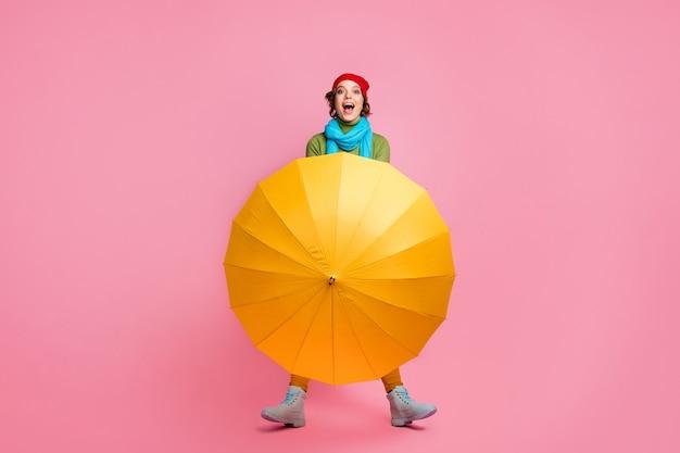 Foto a figura intera della ragazza stupita eccitata goditi la passeggiata invernale del fine settimana nascondi il maglione con il suo parasole aperto indossa calzature alla moda alla moda isolate sopra la parete di colore rosa