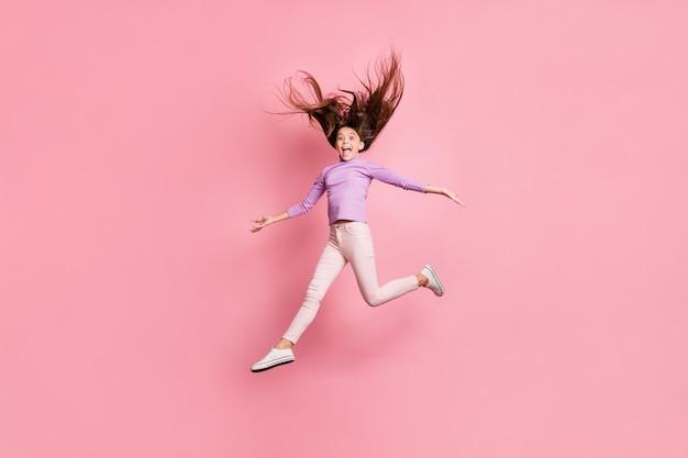 La foto a tutta lunghezza di una ragazzina eccitata che salta si tiene per mano isolata su uno sfondo di colore pastello