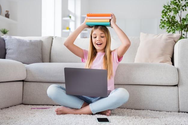 Foto a figura intera di una ragazzina eccitata che lavora a distanza sul laptop avere un tutor online lezione riunione tenere pila pila libri testa sedersi pavimento gambe incrociate piegate in casa al chiuso