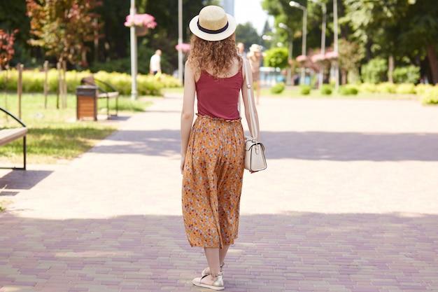 Foto a figura intera dal punto di vista posteriore della giovane snella signora che cammina nell'ombra dell'albero, appassionata di natura, trascorrendo l'ora di pranzo nella zona ricreativa, indossando camicia rossa, gonna arancione, borsa da slitta e cappello di paglia.