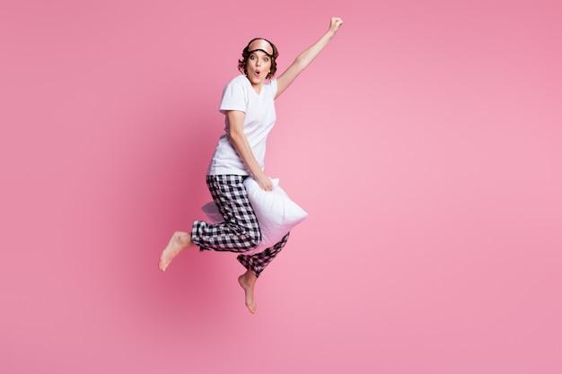Foto integrale della signora pazza divertente che salta il cuscino alto tra il pugno di sollevamento del volo delle gambe