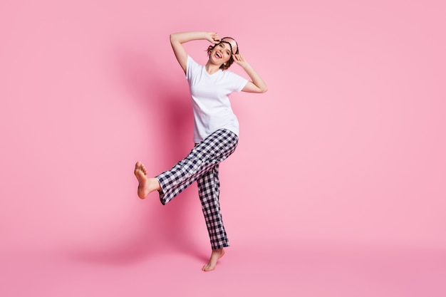 Foto integrale della signora divertente alza la danza delle gambe sulla parete rosa