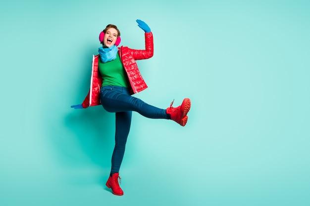 Foto a figura intera di divertente signora a piedi strada alza la gamba alta giocoso buon umore indossare casual cappotto rosso sciarpa rosa paraorecchie pantaloni maglione guanti scarpe isolato verde acqua muro di colore