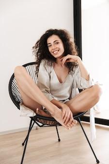 Foto a figura intera di splendida donna con lunghi capelli scuri che indossa abiti di seta per il tempo libero, sorridente mentre era seduto in poltrona in un accogliente appartamento