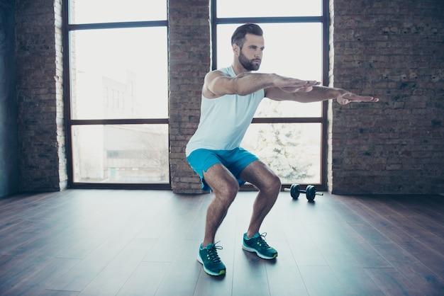 Foto a figura intera di un bel ragazzo allenatore che fa squat statici concentrati di abbigliamento sportivo canotta pantaloncini da ginnastica allenamento a casa vicino alle finestre all'interno