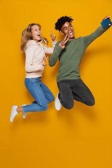 Foto a figura intera di studenti felici uomo e donna 16-18 che ridono e si fanno selfie mentre saltano, isolati su sfondo giallo