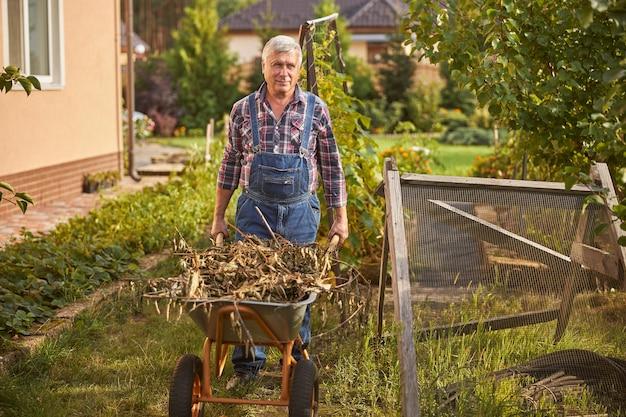 Foto a figura intera di un gioioso uomo dai capelli grigi che spinge un carrello pieno di erbacce secche nel suo giardino