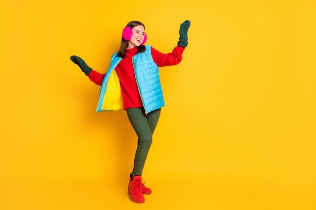Foto a tutta lunghezza di una ragazza allegra positiva che si gode il weekend delle vacanze invernali in discoteca alzando le mani indossa un maglione rosa blu isolato su uno sfondo di colore brillante brillante