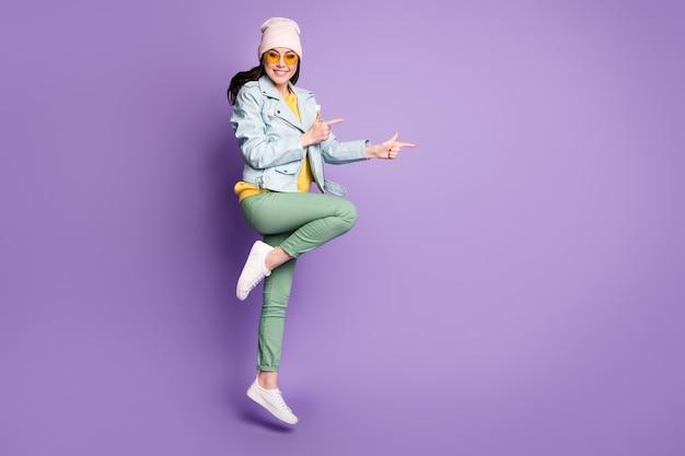 Foto a figura intera positivo ragazza promotore salto punto dito indice copyspace presente annunci promozione consigliare suggerire selezionare indossare giallo verde copricapo occhiali da sole isolato colore viola sfondo