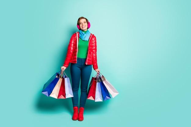 Foto a figura intera ragazza positiva relax centro commerciale acquistare molte borse tenere godere di vacanza turistica autunno primavera indossare pantaloni rossi rosa blu pantaloni maglione verde isolato verde acqua muro di colore