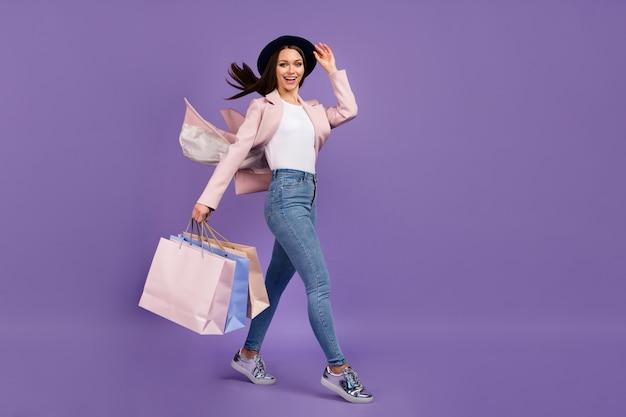 Foto a figura intera ragazza positiva cliente centro commerciale tenere molte borse i suoi capelli volare aria vento lei tocca mano copricapo indossare abito primavera beige denim jeans scarpe isolato colore viola sfondo