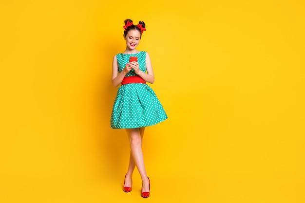 Foto a figura intera di una ragazza positiva che utilizza messaggi di testo su smartphone indossa una gonna verde isolato brillante sfondo di colore brillante