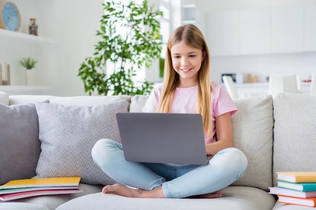 Foto a figura intera di una ragazza intelligente e positiva che studia casa remota usa le informazioni sul progetto di ricerca del laptop sedersi sul divano al chiuso