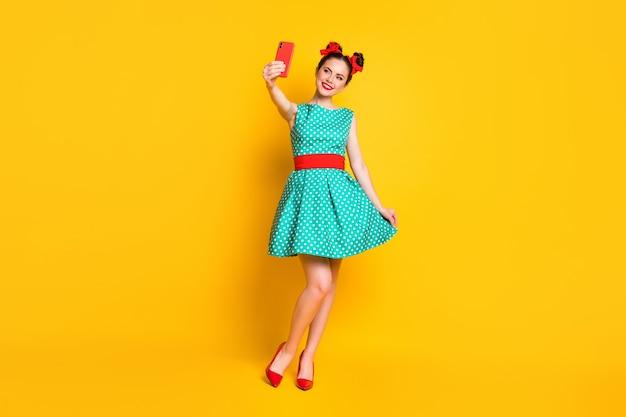 La foto a tutta lunghezza di una ragazza dolce positiva usa lo smartphone per fare selfie con le gambe della gonna a contatto con uno sfondo di colore brillante isolato