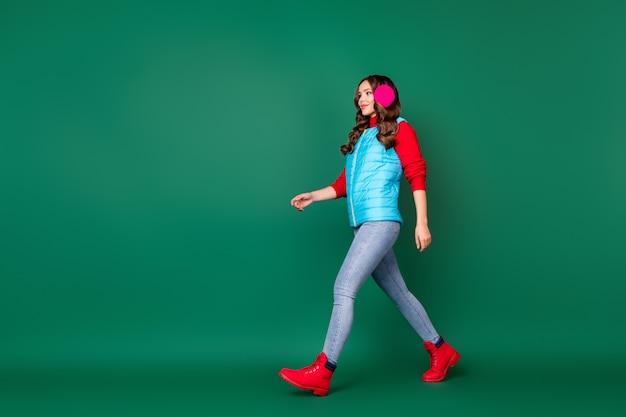 Foto a figura intera di una giovane donna piuttosto affascinante che cammina nel parco cittadino verso casa tempo freddo nevica indossare scaldaorecchie rosa gilet blu jeans maglione rosso stivali isolato sfondo di colore verde