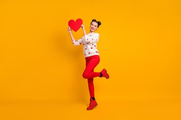 La foto a figura intera del cuore di carta della stretta della signora abbastanza allegra che mostra i sentimenti teneri della cartolina della data indossa le scarpe dei pantaloni del pullover del modello dei cuori rossi bianchi