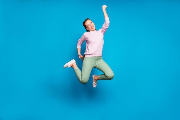 Foto a figura intera di trecce lunghe della signora piuttosto pazza che saltano il campione della competizione sportiva alta indossare pantaloni verdi pullover rosa casual isolati sfondo di colore blu