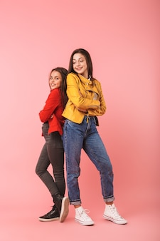 Foto integrale di belle ragazze in casual in piedi insieme, isolato sopra la parete rossa