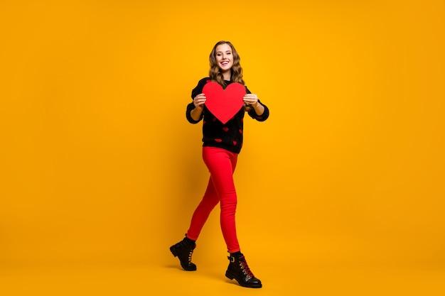 Foto a figura intera di una bella signora che tiene un grande cuore di carta a piedi, idea creativa, data, invito per il ragazzo, indossare, cuori, modello, maglione, pantaloni rossi, scarpe