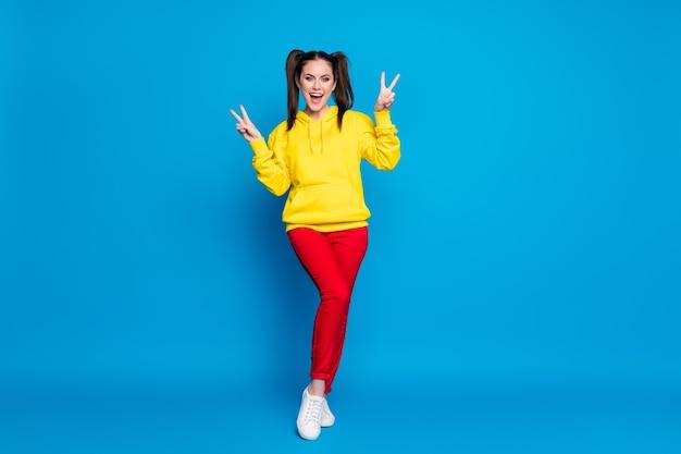 Foto a figura intera di bella signora due code pettinatura che mostra i simboli del segno v buon umore dire ciao amici indossare casual felpa con cappuccio gialla pullover pantaloni rossi scarpe da ginnastica isolate sfondo di colore blu brillante