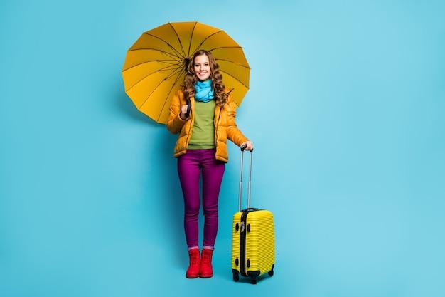 Foto a figura intera di bella signora viaggiatore tenere ombrello borsa rotante valigia attendere viaggio aeroporto indossare cappotto giallo sciarpa blu pantaloni viola stivali isolato parete di colore blu
