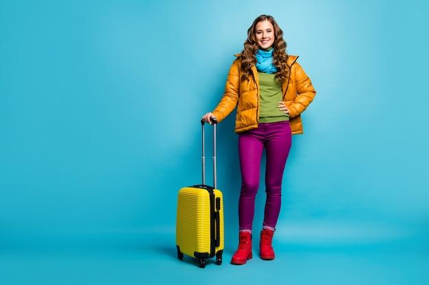 Foto a figura intera di viaggiatore signora piuttosto ondulato tenere la valigia rotolante in attesa registrazione volo aeroporto indossare cappotto giallo sciarpa blu pantaloni scarpe isolato muro di colore blu
