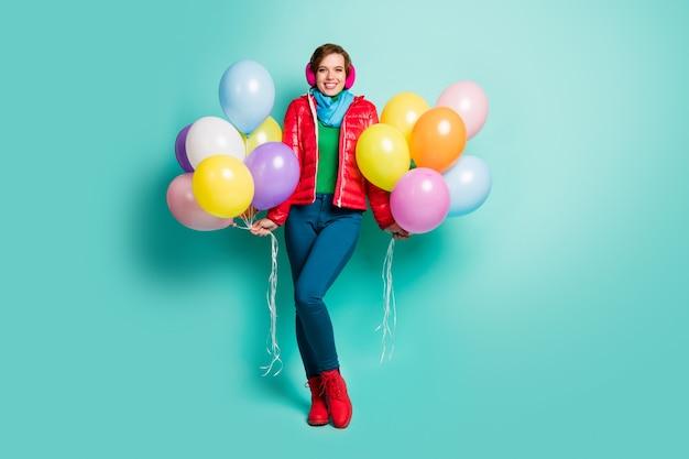 Foto a figura intera di una signora giovane e carina che tiene molti palloncini colorati studenti stagione festa indossare sciarpa cappotto rosso casual paraorecchie rosa pantaloni scarpe vestito isolato muro color verde acqua