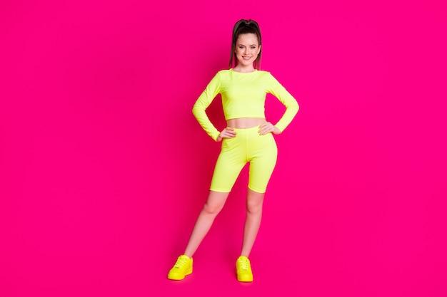 Foto a tutta lunghezza di una donna raggiante e splendente che indossa abiti sportivi mani braccia vita isolato sfondo di colore rosa