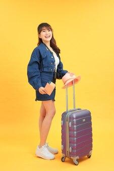 Foto a figura intera di una giovane donna dolce e lucida che tiene in mano il passaporto della valigia isolato sfondo di colore rosa