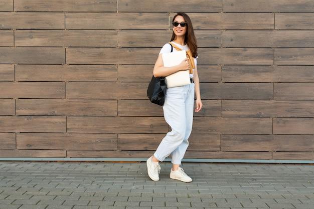 Colpo di foto a figura intera di giovane donna affascinante beautifyl brunet che va in strada vicino al muro marrone