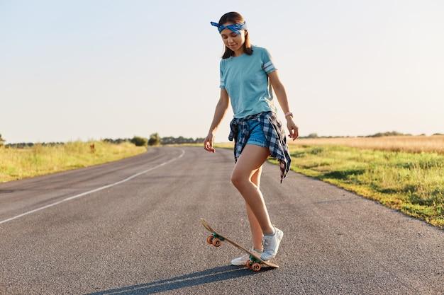 Foto a figura intera di una donna snella e attraente che fa acrobazie su uno skateboard, si diverte da sola per strada, cavalca un longboard, indossa abiti casual, guarda in basso.