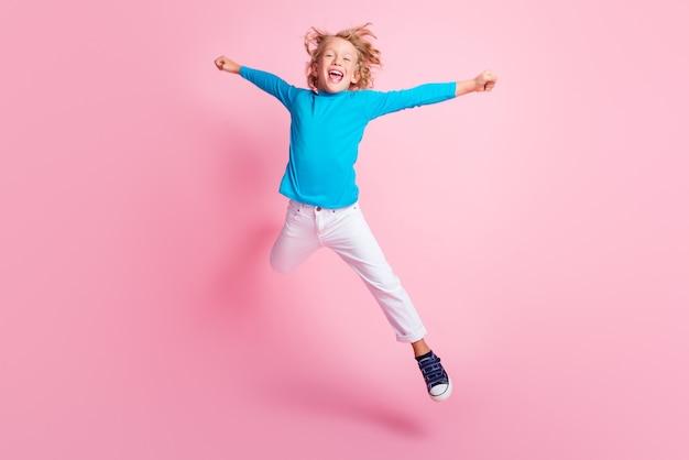Foto a figura intera di un ragazzino che salta in posa con una stella che indossa pantaloni blu a collo alto e scarpe da ginnastica isolate su uno sfondo di colore rosa pastello