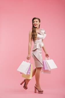 Foto a figura intera di donna sorridente anni '20 in abito che guarda indietro sul copyspace e che tiene i pacchetti della spesa colorati, isolato sopra il muro rosa