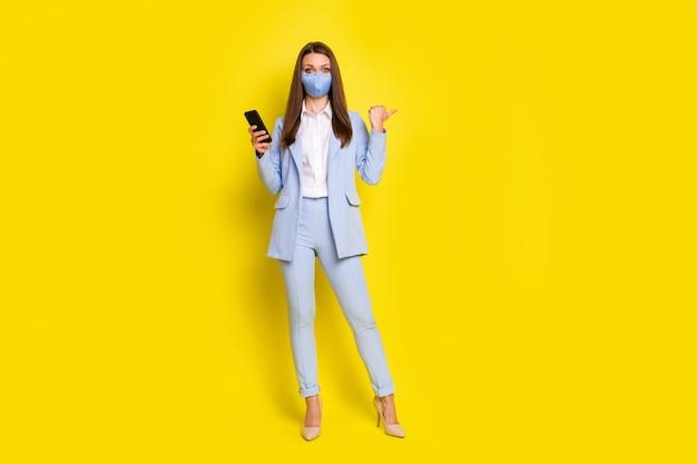 Foto a figura intera smm ragazza usa smartphone segui covid post notizie punto pollice dito copyspace abbigliamento formale abito blu giacca pantaloni stiletti maschera medica isolato giallo colore sfondo